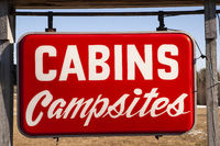 A Red Hanging Roadside Sign Says Cabins and Campsites