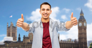 happy young man showing thumbs up over london