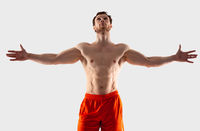 A man in orange shorts with a muscular body spread his arms to the side and looks up
