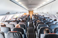 Interior of commercial airplane with passengers on their seats during flight.