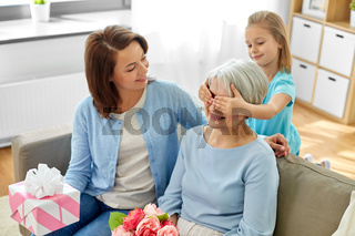 mother and daughter greeting grandmother at home