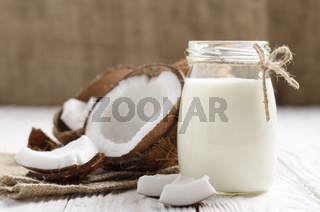 Mason jar of milk or yogurt on hemp napkin on white wooden table with coconut aside