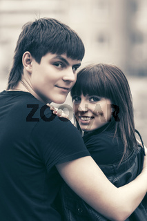 Happy young couple in love hugging in city street