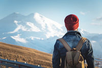 Bearded tourist hipster man in sunglasses with a backpack stand back on a roadside bump and watching the sunset against the background of a snow capped mountain