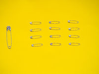A large safety pin followed by other smaller ones in human representation. Leadership concept