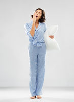 sleepy woman in pajama holding pillow and yawning