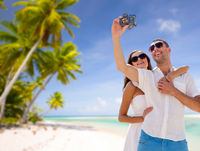 couple making selfie by camera over tropical beach