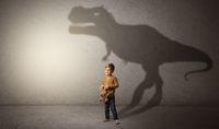 Dinosaurus shadow behind cute boy