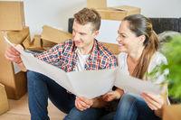Paar mit Bauplan bei Planung von Hausbau