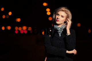 Fashion blond woman in black coat walking in a night city street