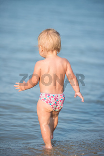 Cute baby playing on the sandy beach and in sea water.