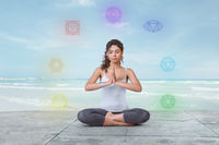 Young yogi woman is meditating on the beach in lotus position with chakras glowing around her