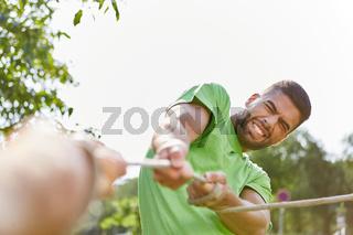 junger Mann beim Wettkampf im tauziehen