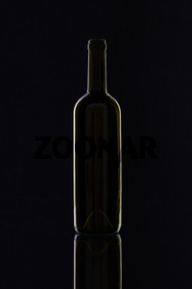 Silhouette of elegant and very old wine bottle on a glass desk