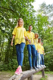 Junge Leute als Team auf dem Balancierbalken