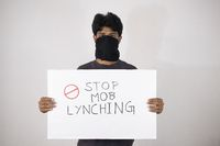 Young man protesting against the Mob lynching by holding Placard showing of Stop Mob Lynching on isolated background.