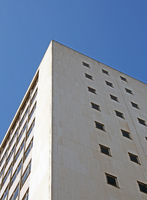 perspective corner view of an old white 1960s concrete office block against a blue sky