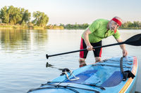 senior paddler with stand up paddleboard