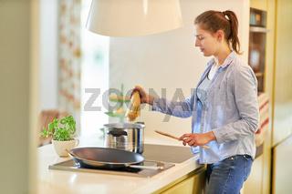 Junge Frau am Herd in der Küche macht Spaghetti