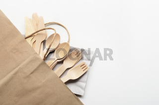 Wooden single use kitchenware in paper shopping bag on white. Top view, space for text.