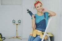 Happy woman with drill sitting on stepladder