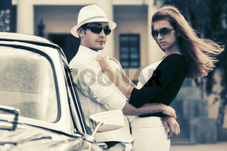 Happy young fashion couple in love outside a vintage car