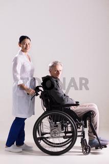 Nurse pushing wheelchair with man in it.