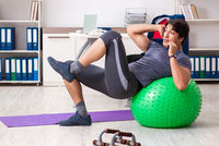 Young male employee exercising in the office