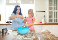 Happy young mother and her daughter pouring flour through sieve for dough