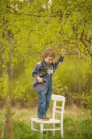 Young blonde boy standing on white old chair under birch tree in outdoor.