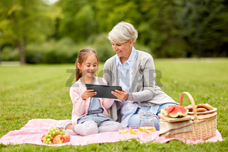 grandmother and granddaughter with tablet at park