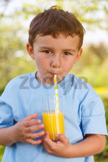 Kind kleiner Junge trinkt Orangensaft Saft trinken Hochformat draußen Natur