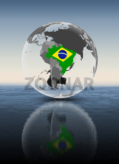 Brazil on translucent globe above water