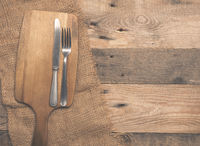 Old flatware with cutting board on wood