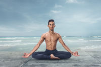 Young yogi man is meditating on the beach in lotus position