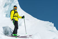 A freerider skier in complete outfit stands on a glacier in the North Caucasus