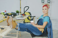 Female relaxing at carpenter workbench with drink