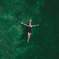 Aerial view of woman lying on the grass