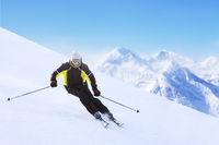 Alpine skier on piste running downhill