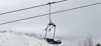 Chair lift and snowy mountains in haze