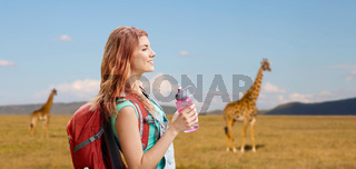 happy woman with backpack over african savannah