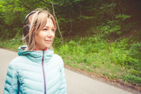 Portrait of an attractive sports girl blonde in a light running down jacket dressing bluetooth headphones with music or the sounds of nature while on a forest road