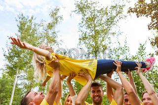 Junge Leute heben eine Frau in Teamwork
