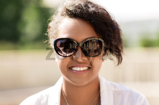 happy african american young woman in sunglasses