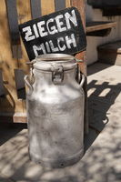 A milk churn filled with lactose free goat milk on a farm. German word Ziegenmilch means Goat milk.