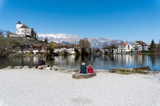 Werdenberg, SG / Switzerland - March 31, 2019: tourists enjoy a visit to idyllic and historic Werdenberg village and lake with a great view of the Swiss Alps in the background