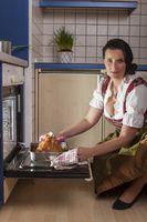 Bayerische Frau in einem Dirndl beim Kochen