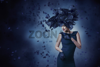 Fashion portrait of young woman posing in fantasy hat