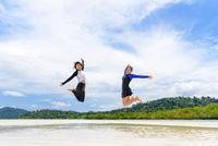 Two asian teen girls friends jumping enjoy on the beach