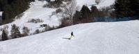 Snowboarder on ski slope at sun winter day